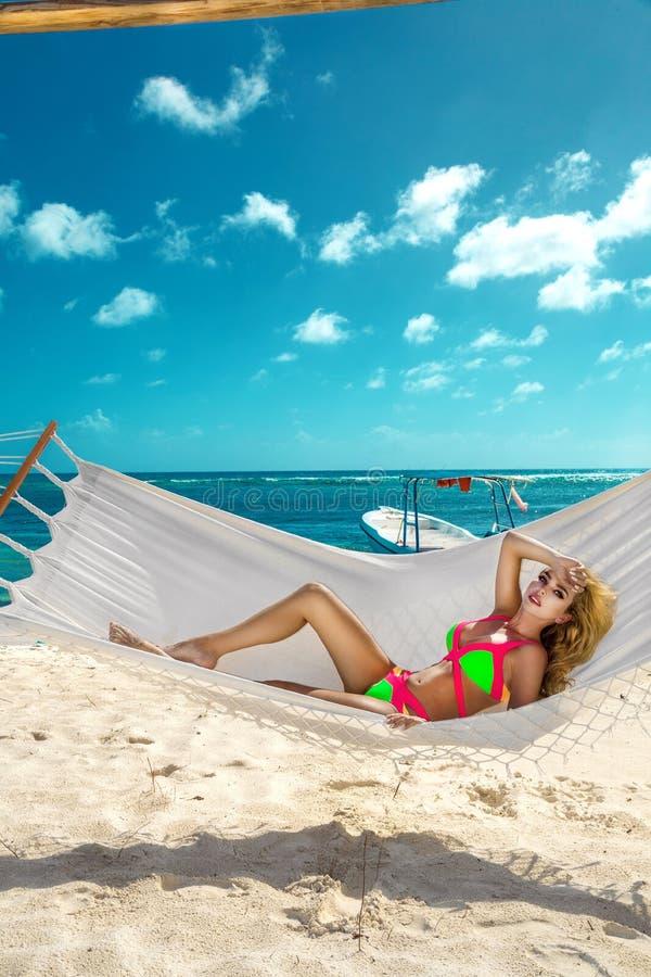 Lycklig sexig och h?rlig kvinna som ligger i h?ngmattan p? stranden med en underbar vit sand - bild arkivfoton