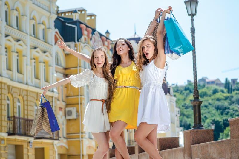 Lycklig shopaholicsflickvän Tre flickvänner som rymmer shopping arkivfoto