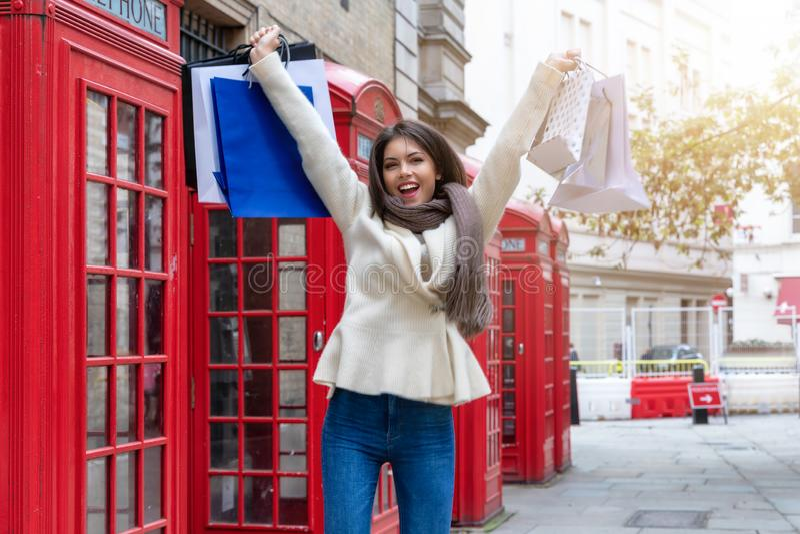 Lycklig shoppa kvinna med shoppingpåsar i hennes hand, London, UK arkivbild