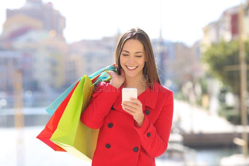 Lycklig shoppareturist som använder en telefon i vinter arkivfoto