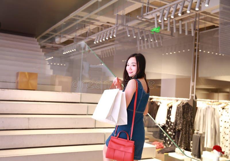 Lycklig shopping för Asien kinesisk östlig orientalisk ung moderiktig kvinnaflicka i galleria med påsar royaltyfri bild