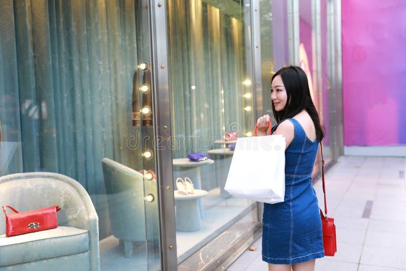 Lycklig shopping för den Asien kinesisk östlig orientalisk ung moderiktig kvinnaflickan i galleria med påsar ser shoppingfönstret royaltyfria foton