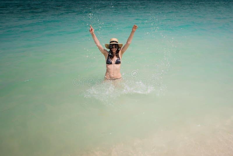 Lycklig simning för ung kvinna i det azura havet Rolig flicka i sugrörhatt arkivbilder