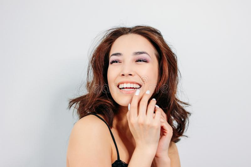 Lycklig sinnlig le asiatisk ung kvinna för flicka med mörkt långt lockigt hår i svart underkläder på vit bakgrund royaltyfri fotografi