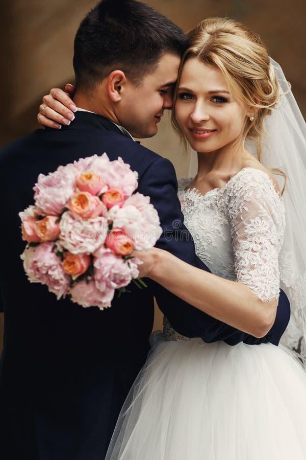 Lycklig sinnlig stilig brudgum och blond härlig brud i vit royaltyfria foton
