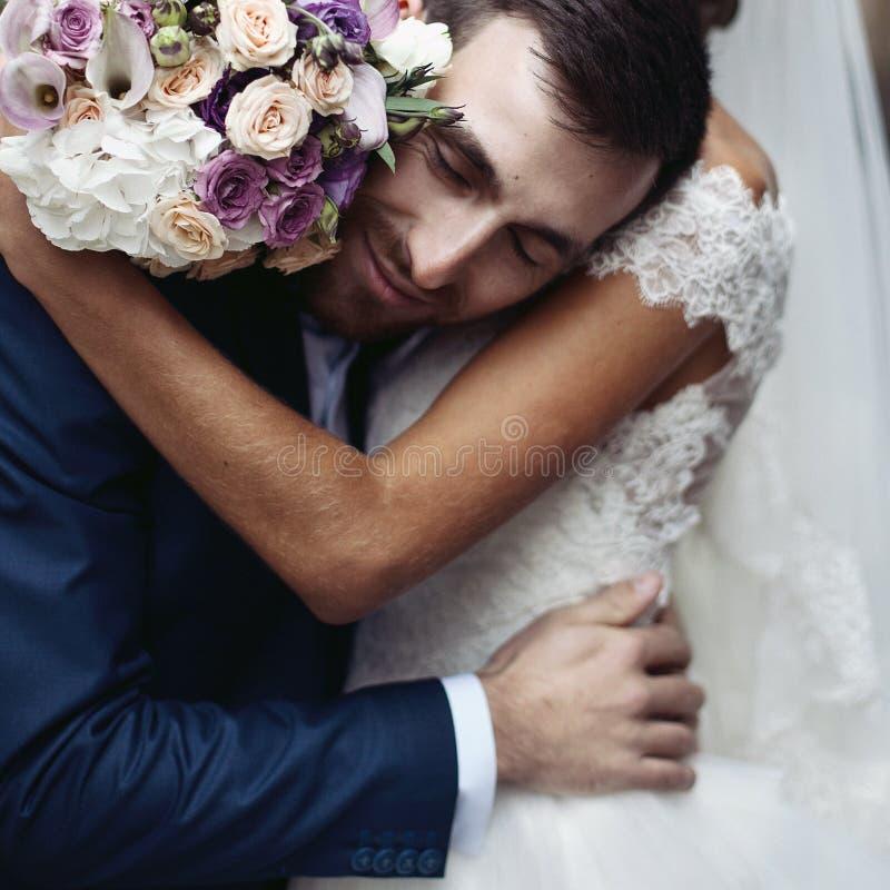 Lycklig sinnlig stilig brudgum som kramar den härliga bruden med bouque royaltyfri foto