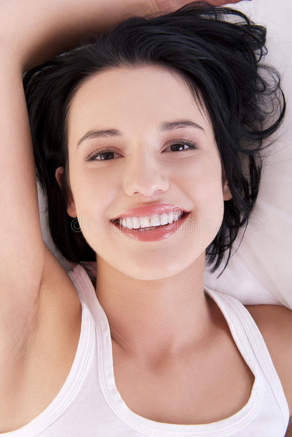 Lycklig sinnlig ung kvinna som ligger i underlag royaltyfria foton