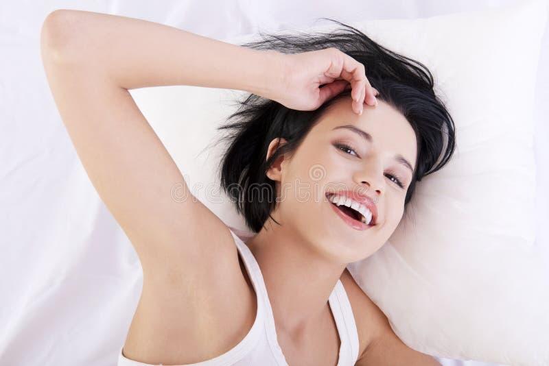 Lycklig sinnlig ung kvinna som ligger i underlag arkivfoto