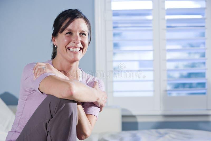 lycklig sittande le kvinna för soffa royaltyfria bilder