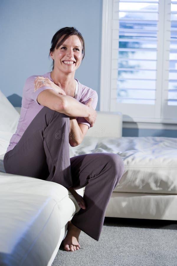 lycklig sittande le kvinna för soffa royaltyfri fotografi