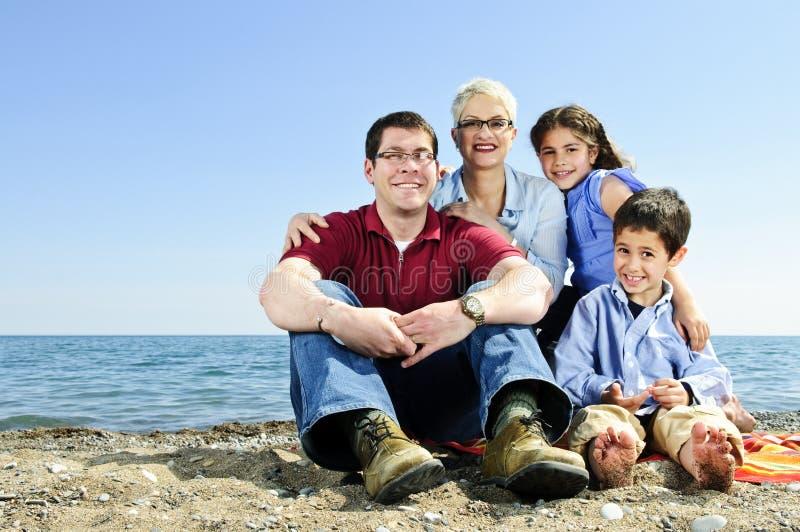 lycklig sitting för strandfamilj arkivbild
