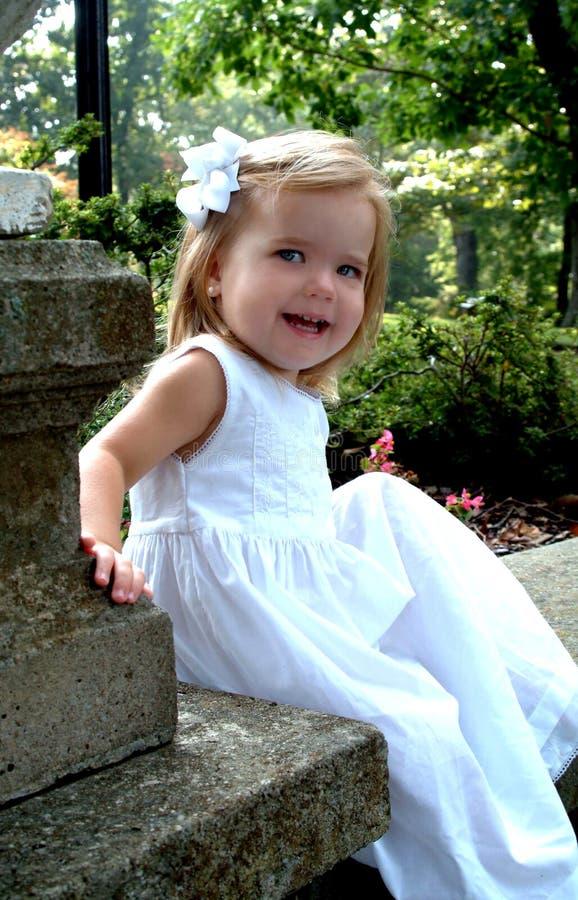 lycklig sitting för trädgårds- flicka arkivfoton