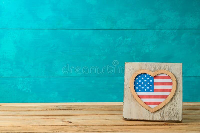 Lycklig sj?lvst?ndighetsdagen, 4th av det Juli ber?mbegreppet med ramen och amerikanska flaggan p? tr?tabellen royaltyfri fotografi