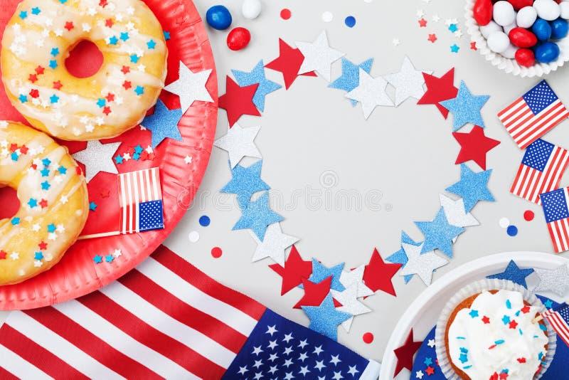 Lycklig självständighetsdagen4th juli bakgrund med amerikanska flaggan dekorerade av söta foods, stjärnor och konfettier Ferietab royaltyfri fotografi