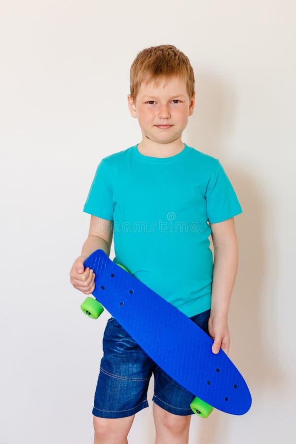 Lycklig sju-år-gammal pojke i en turkost-skjorta som rymmer en ny blå skridsko arkivfoto