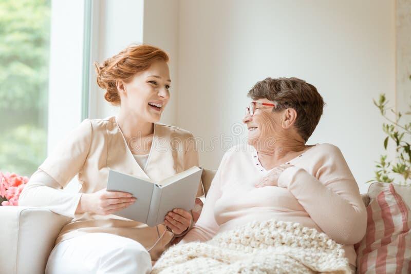 Lycklig sjuksköterska som läser en rolig bok till hennes äldre patient i en pri arkivbild