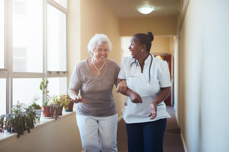 Lycklig sjukvårdarbetare och pensionärkvinna som tillsammans talar royaltyfri foto
