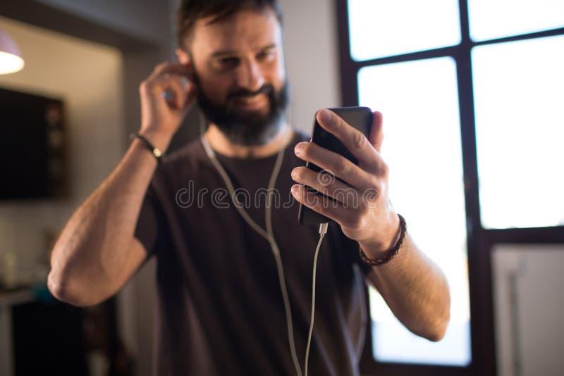 Lycklig skäggig grabb som bär tillfällig grå t-skjorta lyssnande musik i hörlurar som kontrollerar sociala nätverk på smar arkivbilder