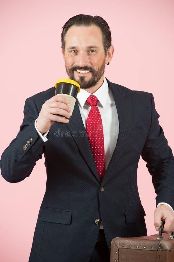 Lycklig skäggig man i blått följe och rött band som dricker kaffe Affärsmän i lopp royaltyfria bilder