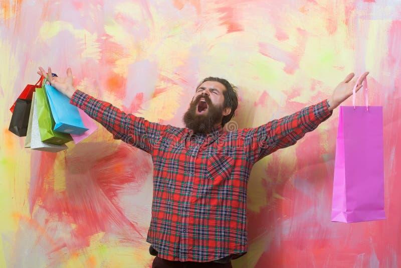 Lycklig skäggig man som ropar med färgrika pappers- shoppingpåsar royaltyfri foto