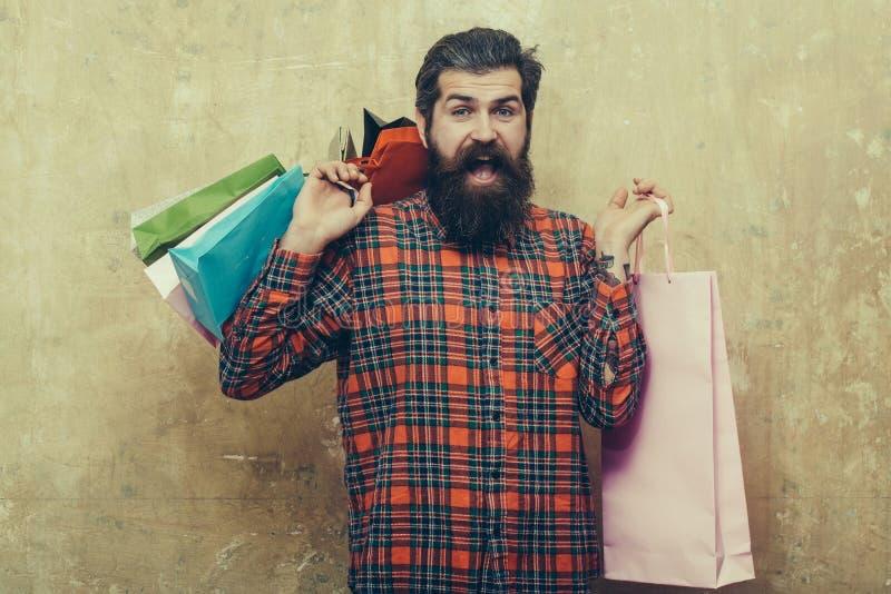 Lycklig skäggig man som rymmer färgrika pappers- shoppingpåsar arkivbild