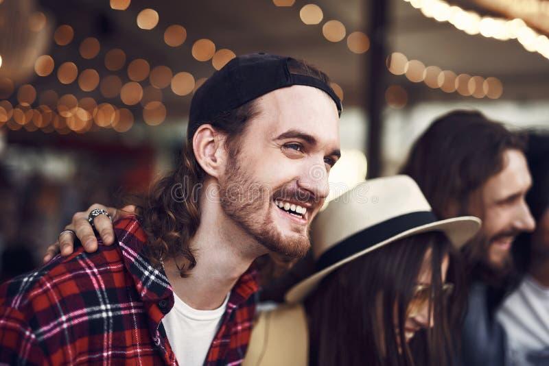 Lycklig skäggig man som skrattar, medan stå med vänner utomhus arkivfoton
