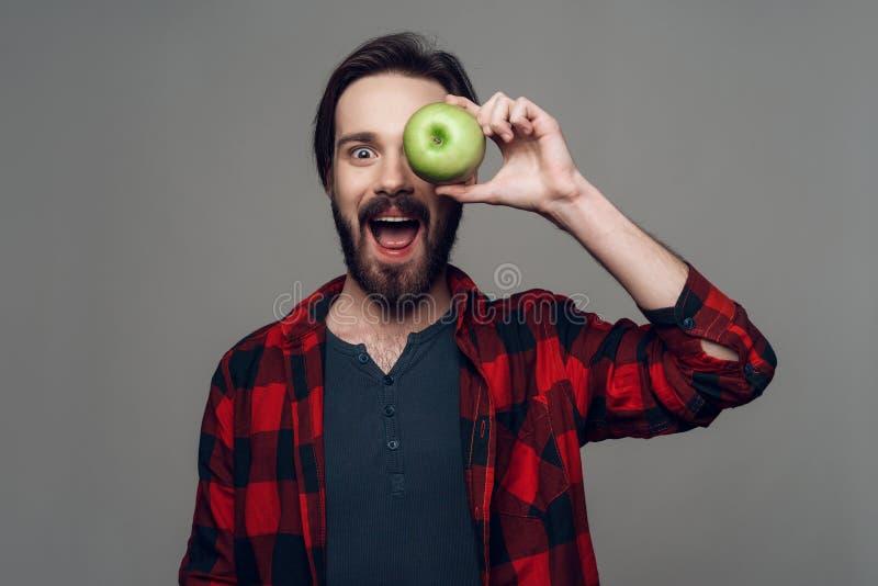 Lycklig skäggig manhåll Apple och se kameran arkivfoton