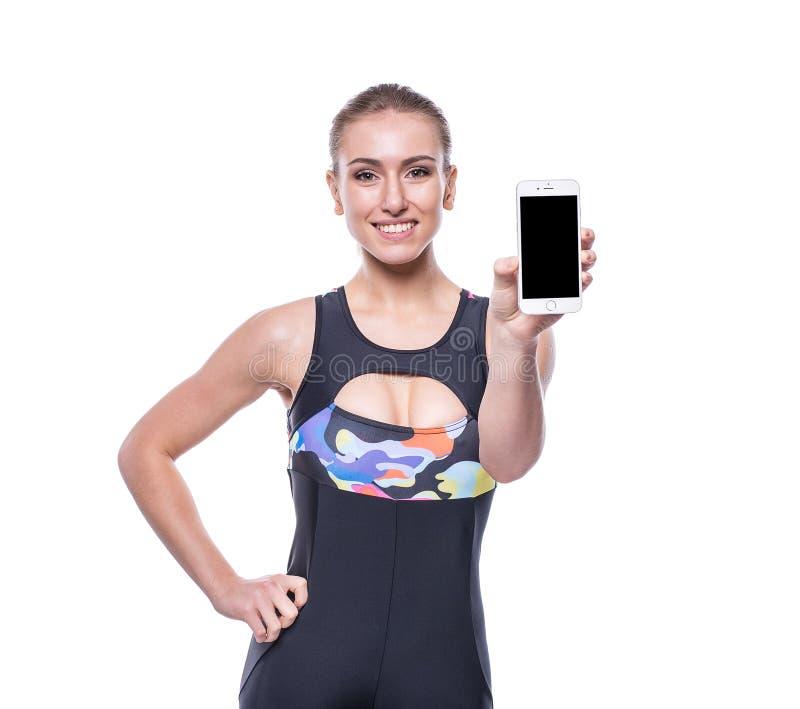 Lycklig skärm för smartphone för mellanrum för visning för träningsoverall för sportswear för ung kvinna för kondition som bärand royaltyfri fotografi