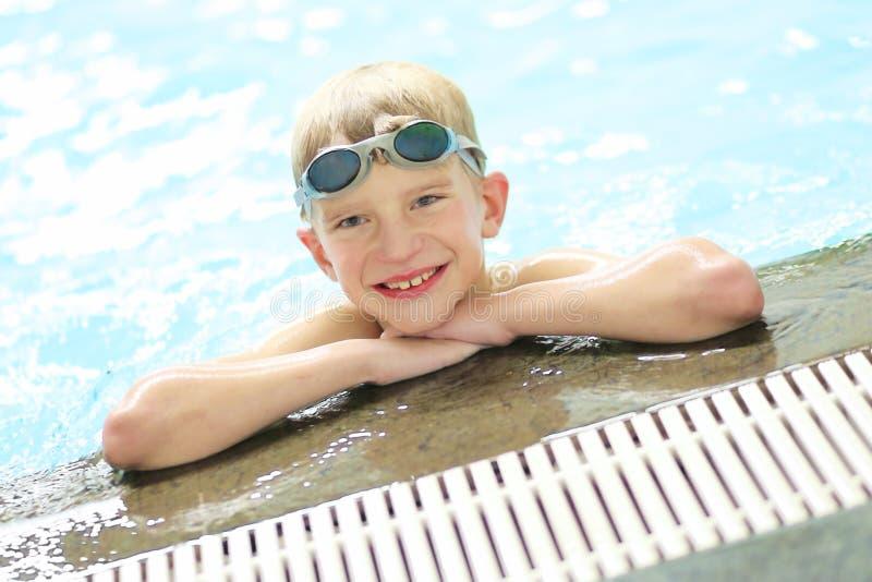 Lycklig skolapojke med skyddsglasögon i simbassäng arkivbilder