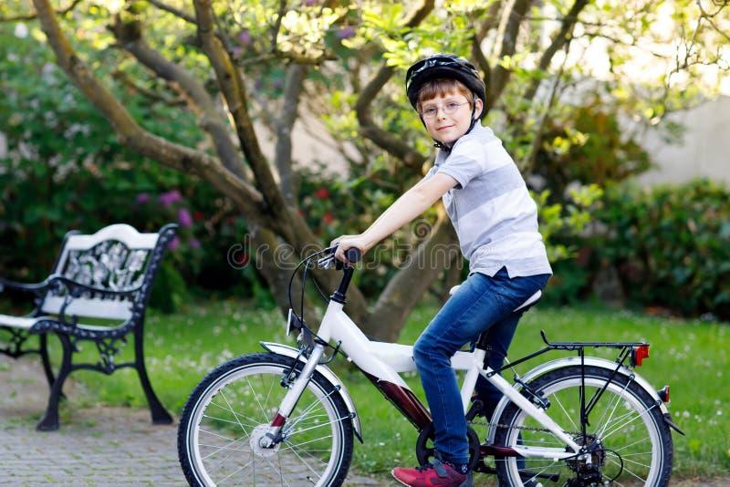 Lycklig skolaungepojke som har gyckel med ridning av cykeln Aktivt sunt barn med sportar för danande för säkerhetshjälm med cykel royaltyfri foto