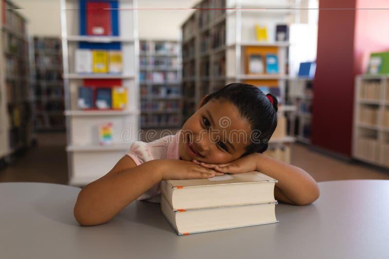 Lycklig skolflicka som lutar på böcker och ser kameran på tabellen i skolaarkiv arkivfoto
