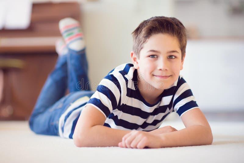 Lycklig skolpojke 9 år gammalt ligga på golv arkivbild