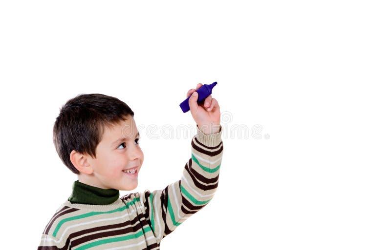 Lycklig skolpojke som skriver något royaltyfri bild