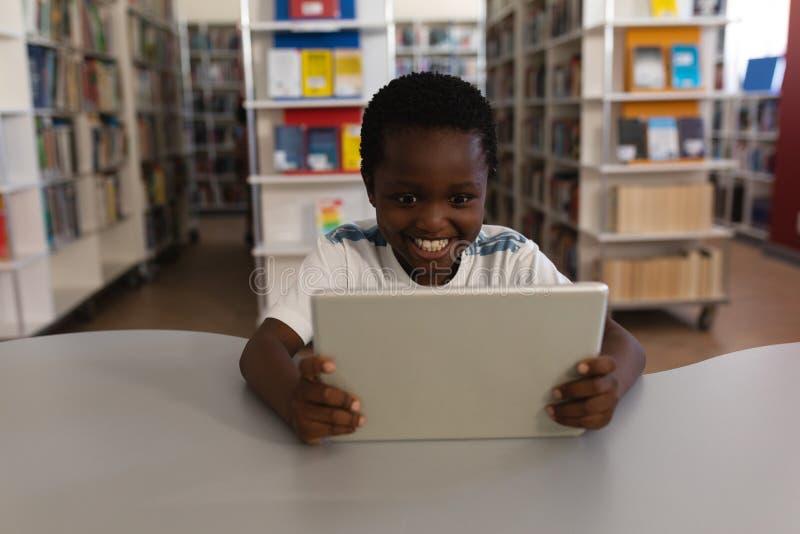 Lycklig skolpojke som studerar på den digitala minnestavlan på tabellen i skolaarkiv arkivfoton