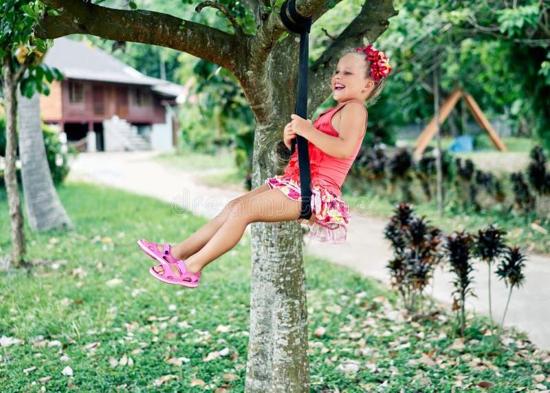 Lycklig skratta barnflicka på gunga utomhus royaltyfri fotografi