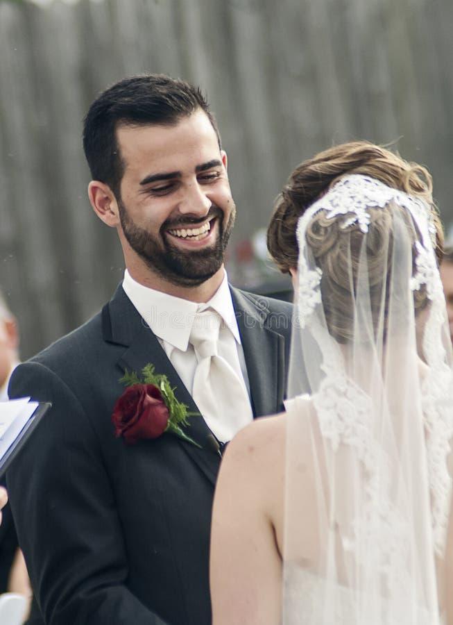 Lycklig skratta brudgum under bröllop royaltyfria foton