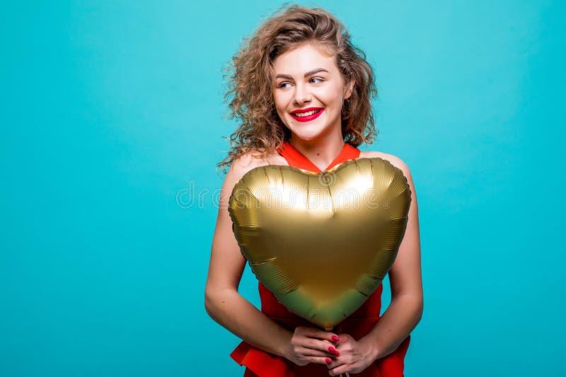 Lycklig skratta kvinna för stående i röd klänning, en guld- ballong i formen av en hjärta på blå bakgrund fotografering för bildbyråer