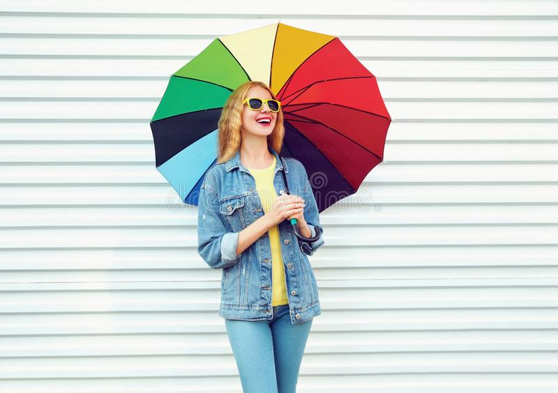 Lycklig skratta kvinna med det färgrika paraplyet i höstdag på den vita väggen arkivbilder
