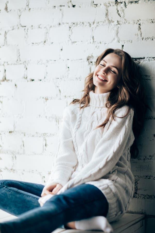 Lycklig skratta kvinna som kopplar av på bakgrund för tegelstenvägg arkivfoto