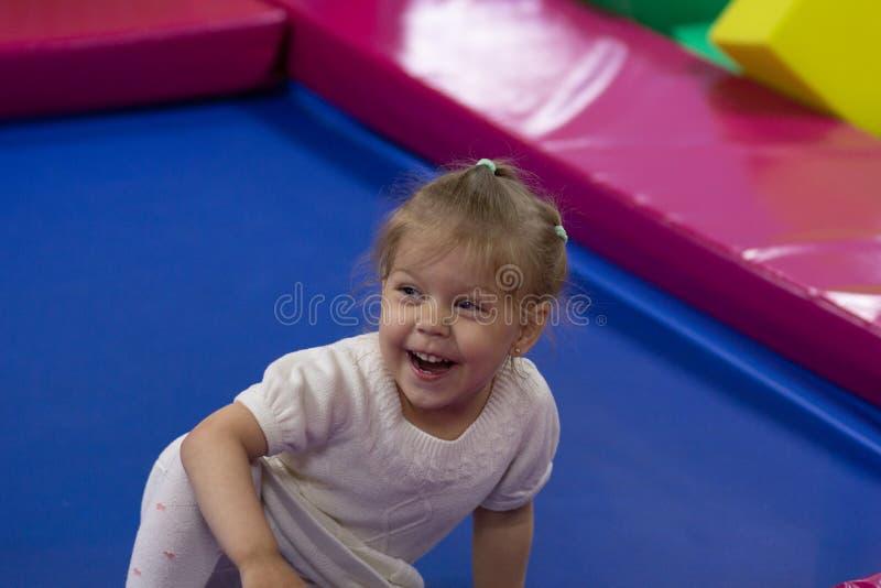 Lycklig skratta liten flicka som sitter på golv i lekrum royaltyfri bild