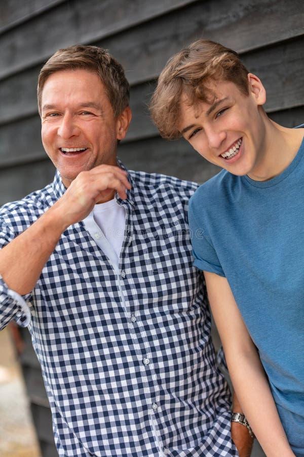 Lycklig skratta mitt åldras fader- och tonåringson fotografering för bildbyråer