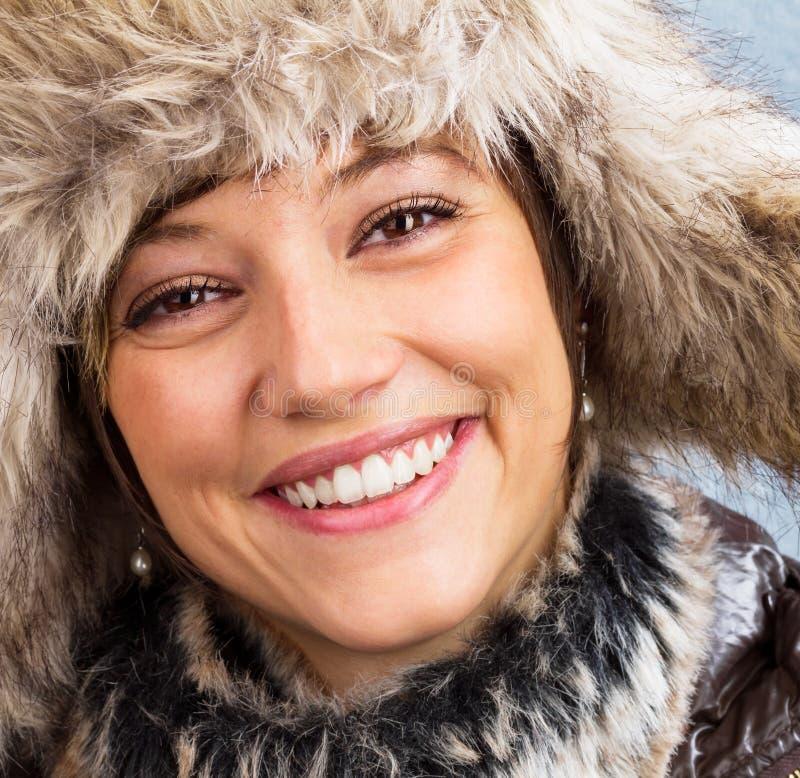 Lycklig skratta ung kvinna med pälshatten royaltyfri foto