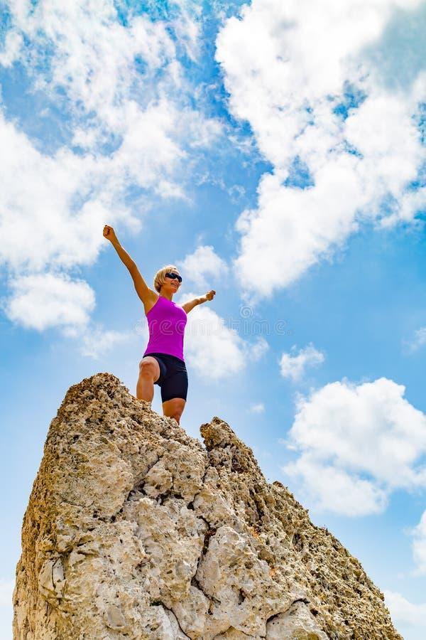 Lycklig slingalöparevinnare som når kvinnan för livmålframgång arkivbilder