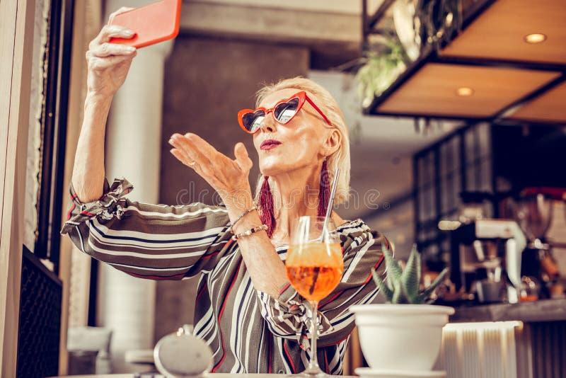 Lycklig snygg elegant gammal dam som poserar, medan göra selfie royaltyfri fotografi