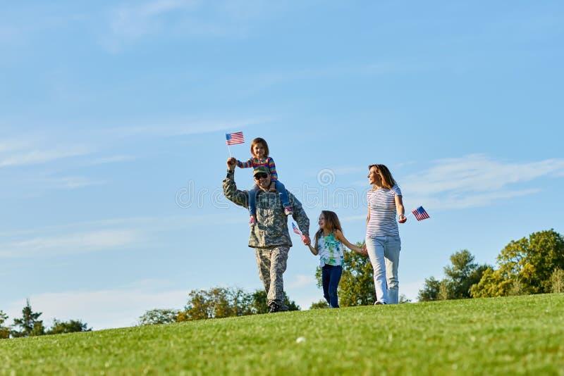 Lycklig soldat med familjen utomhus fotografering för bildbyråer