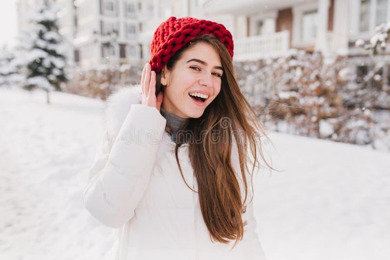 Lycklig solig djupfryst morgon på vintertid av den glade unga kvinnan i röd hatt, med långt brunetthår som har gyckel på gatan royaltyfri fotografi
