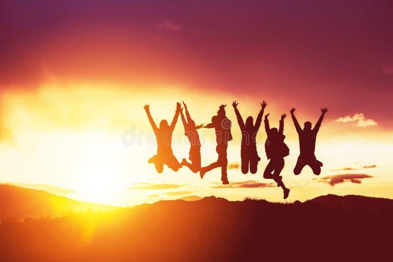 Lycklig solnedgång för vänkonturhopp arkivfoton