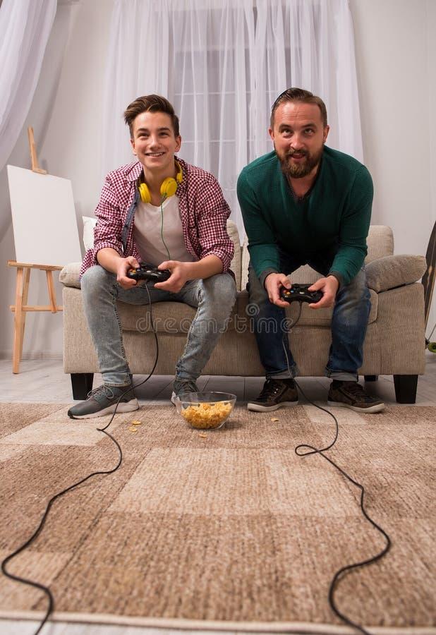 Lycklig son och fader som tillsammans spelar videospelet arkivbilder