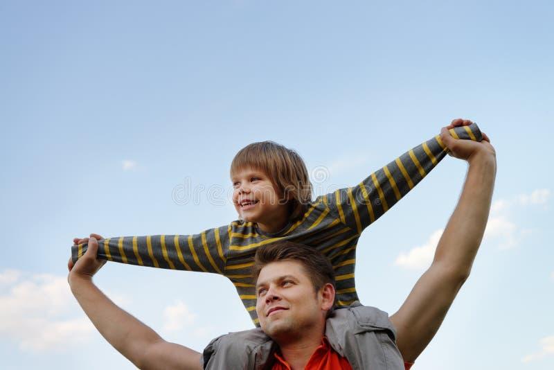 Lycklig son på skulderna av fadern royaltyfri foto