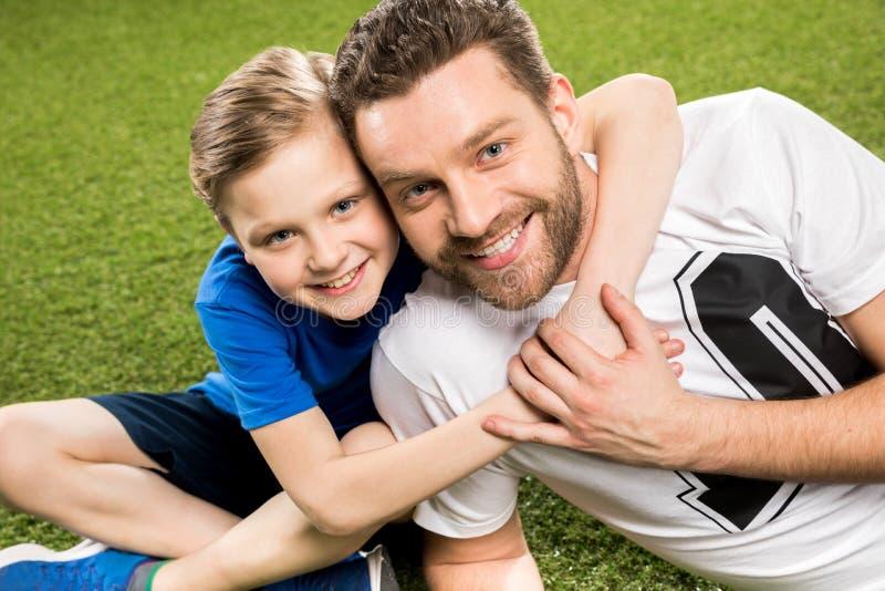 Lycklig son som kramar le fadern, medan ligga på gräs royaltyfri foto